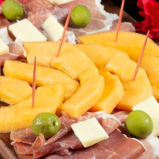 A plate full of Proscuitto, cheese and melon