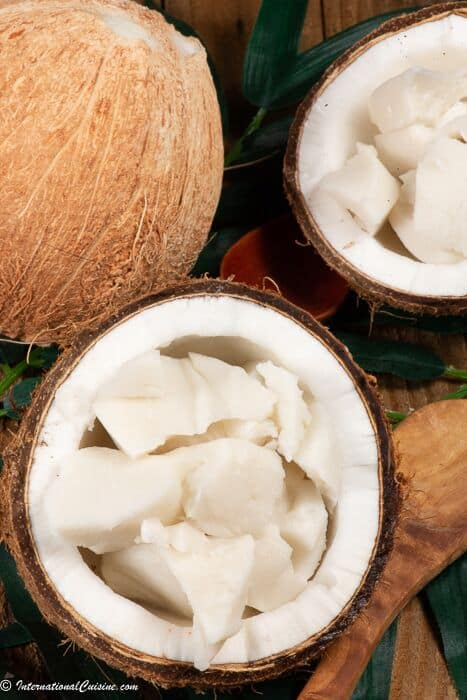 a half coconut filled with pieces of coconut pudding