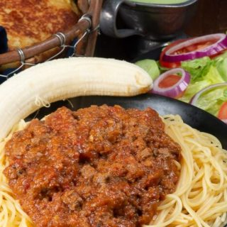 A plate full of pasta topped with Somali Pasta sauce called suugo along with a banana.