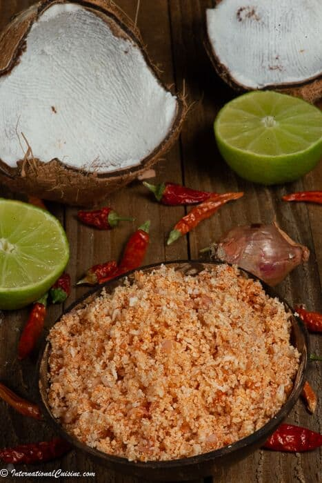 A bowl full of pol sambol with coconut, lime, shallot and red chilies as the ingredients.