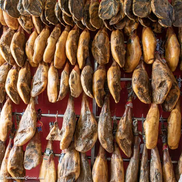 A wall full of jamon hanging in a market