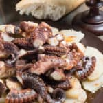 a plate with boiled potatoes topped with tender octopus