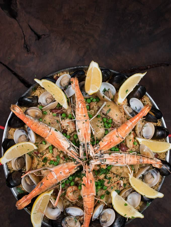 A pan full of paella rice topped with meats and seafood.