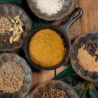 Sri Lankan roasted curry powder surrounded by the ingredients that make it. Coriander seed, cumin seed, whole clove, black peppercorns, black mustard seed, fennel seed, basmati rice, cardomom pods.