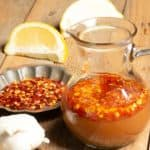 a container with a popular hot sauce in Sudan called shata it has hot chili flakes, garlic and lemons.