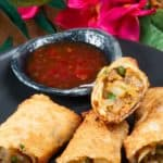A plateful of Surinamese Spring rolls called loempia surround a sweet chili dipping sauce.