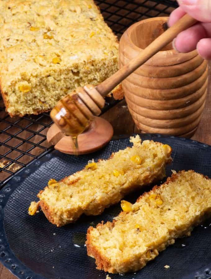 a couple slices of mealie bread being drizzled with some honey.