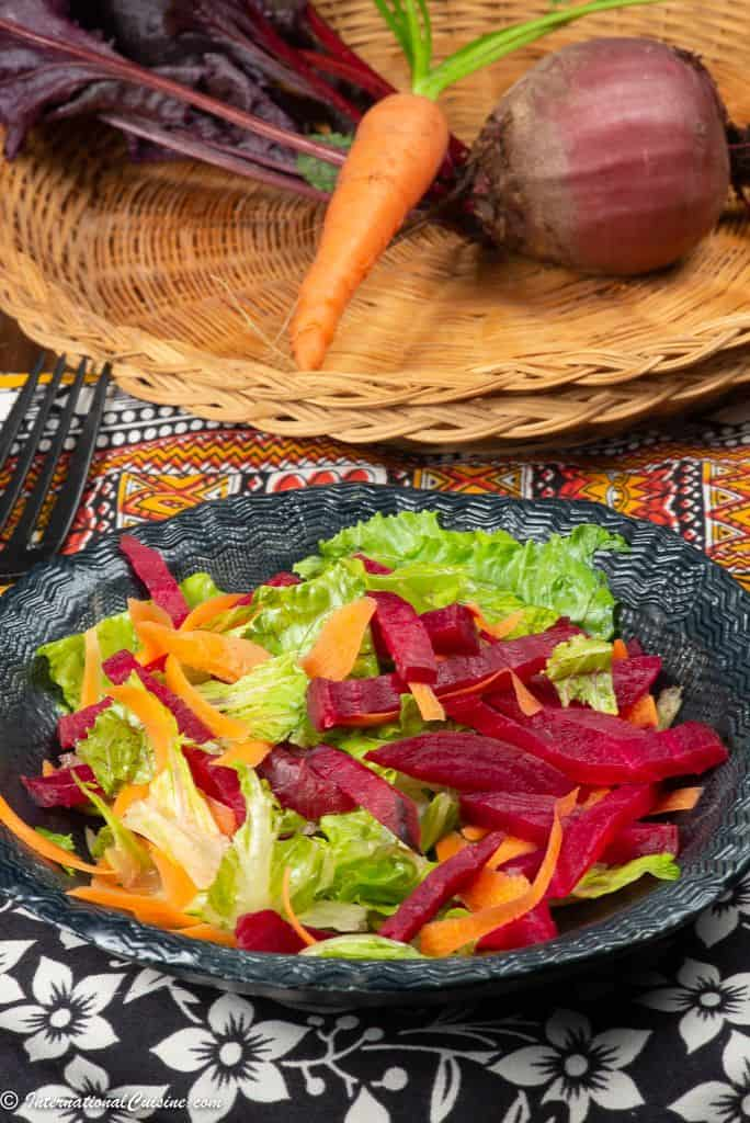 a salad with letttuce, beets and carrots