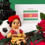 Symbols of Suriname a picture of the falg, a ship, a soccor ball and theit national flower