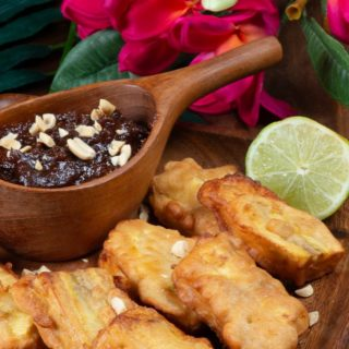 a plateful of battered and fried plantains served with a spicy peanut sauce