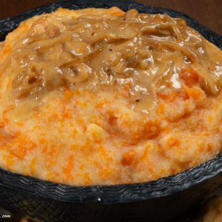 A bowl full of pumpkin pap served with a little cream sauce and onions.