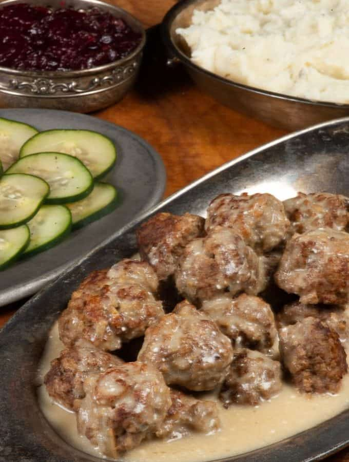 A plateful of swedish meatballs served with mashed potatoes, lingonberry sauce and cucumber salad.