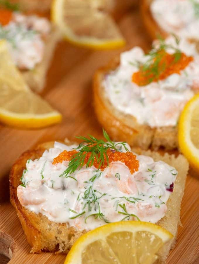 A plateful of Toast Skagan, shrimps in a mayonaise mixture topped with caviar, garnished with dill and a thin slice of lemon.