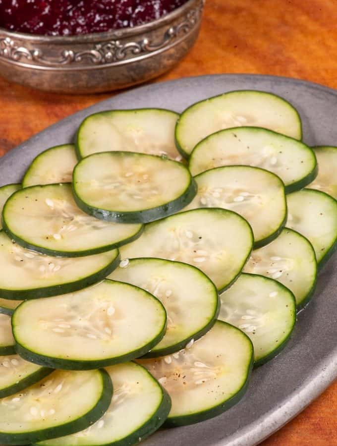 a plateful of thinly sliced pickled cucumbers called pressgurka in Sweden.