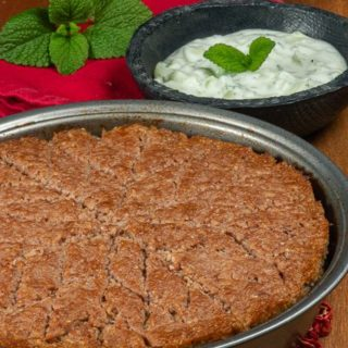 A baked lamb kibbeh cut into diamond pieces and served with greek yogurt.