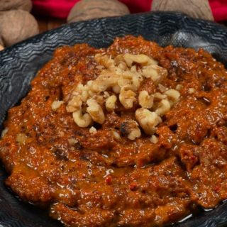 A bowl full of muhammara, a syrian red pepper sauce garnished with walnuts and surrounded by pita.