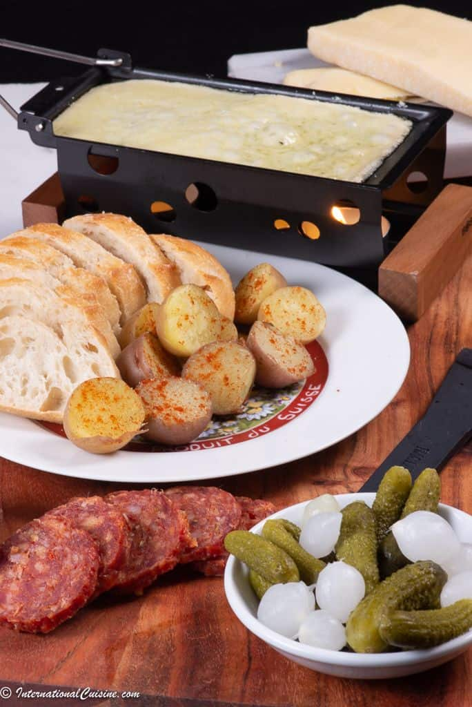 A raclette grill with melted bubbly cheese ready to put on boiled potatoes, bread, cured meat and gherkins with onions.