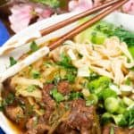 A bowl of Taiwanese beef noodle soup with chopstickes and plum blossoms