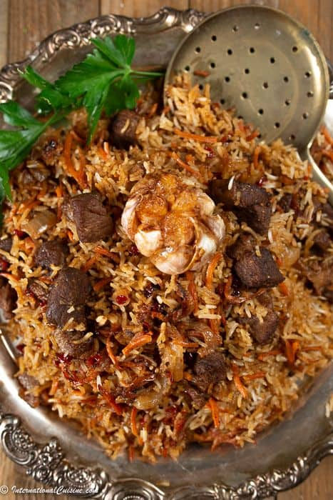 a platter full of Uzbek plov with lamb pieces, carrots, a whole roasted garlic and of course seasoned rice.