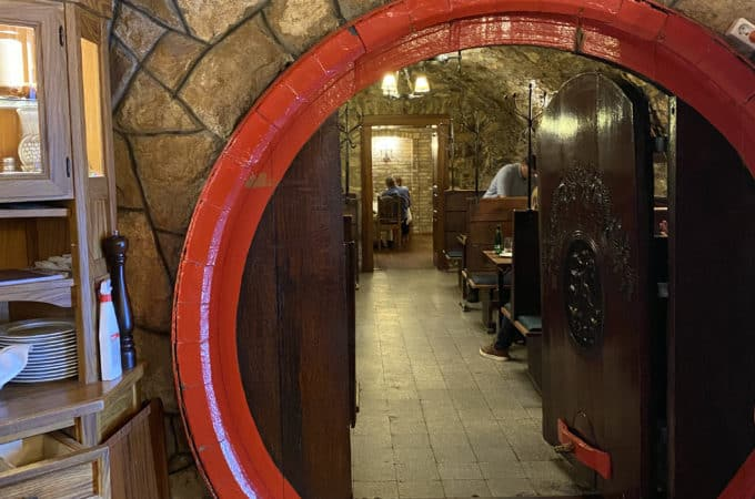 A picture of a head hoop of a large wine barrel which serves as a doorway into the restaurant